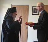 Parish Council Presidente, Gene Rebeck greets Archbishop Job on Sunday morning.